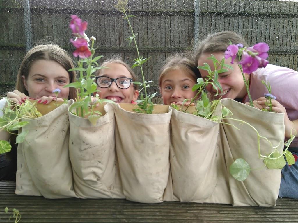 Girls peeking from behind plants